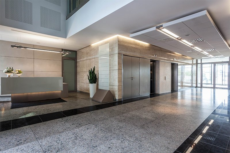 Corporate lobby viewing elevators and front desk with recessed track lighting along the walls, floors, and under desks