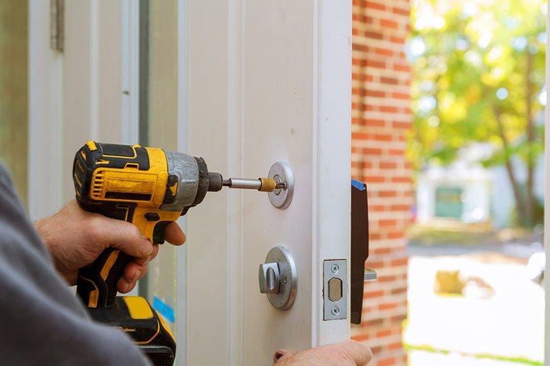 Handyman working on a home's smart lock