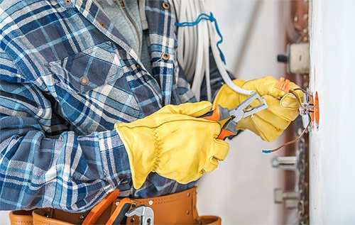 Electrician with protective gloves cutting wires
