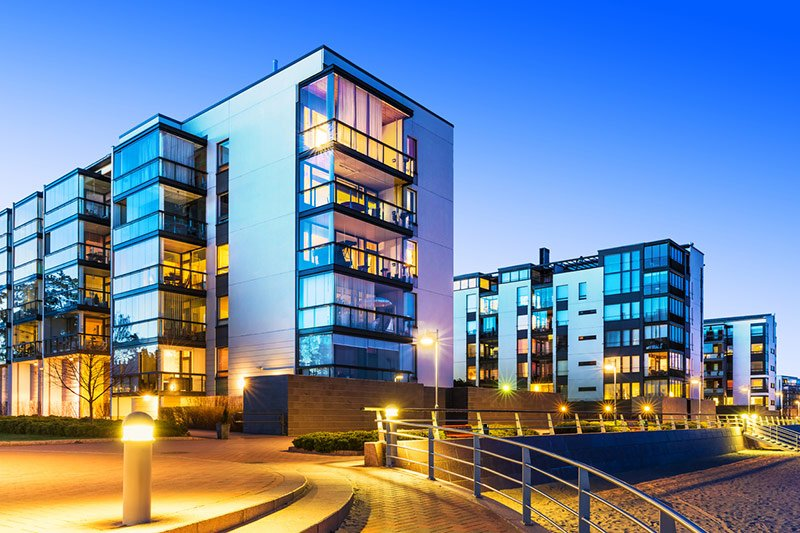 Well lit commercial office buildings and courtyard at night with lights along the stairs and landscaping