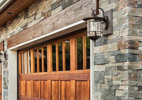 Wooden garage door with natural stone home exterior and industrial style lantern lighting on each side