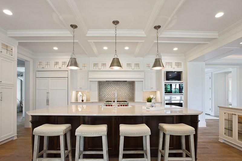 Well lit and all white aesthetic home kitchen with recessed ceiling lights, hanging lamps above the island, and lit backsplash
